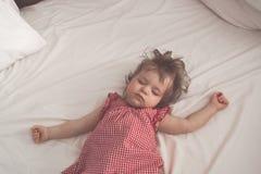 Behandla som ett barn flickan som sover på baksida med öppna armar och utan fredsmäklaren i en säng med vita ark Fridsamt sova i  arkivbilder