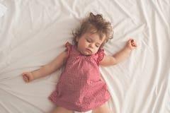 Behandla som ett barn flickan som sover på baksida med öppna armar och utan fredsmäklaren i en säng med vita ark Fridsamt sova i  royaltyfria bilder