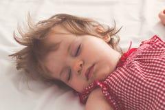 Behandla som ett barn flickan som sover på baksida med öppna armar och utan fredsmäklaren i en säng med vita ark Fridsamt sova i  royaltyfri bild