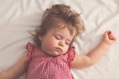 Behandla som ett barn flickan som sover på baksida med öppna armar och utan fredsmäklaren i en säng med vita ark Fridsamt sova i  fotografering för bildbyråer