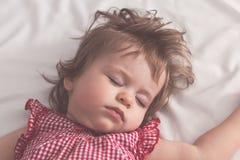 Behandla som ett barn flickan som sover på baksida med öppna armar och utan fredsmäklaren i en säng med vita ark Fridsamt sova i  royaltyfri fotografi