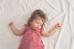 Behandla som ett barn flickan som sover på baksida med öppna armar och utan fredsmäklaren i en säng med vita ark Fridsamt sova i  royaltyfria foton