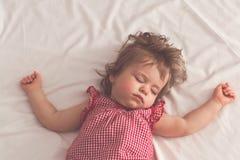 Behandla som ett barn flickan som sover på baksida med öppna armar och utan fredsmäklaren i en säng med vita ark Fridsamt sova i  arkivfoto