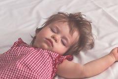 Behandla som ett barn flickan som sover på baksida med öppna armar och utan fredsmäklaren i en säng med vita ark Fridsamt sova i  arkivbild