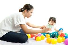 Behandla som ett barn flickan spelar bollen med hennes moder Royaltyfri Bild