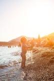 Behandla som ett barn flickan spelar i havet på en solnedgång Arkivfoto