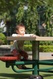 A behandla som ett barn flickan spelar i parkerar med den lyckliga framsidan arkivbild