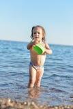 Behandla som ett barn flickan spelar i vattnet Arkivbild