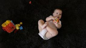 Behandla som ett barn flickan som spelar med färgrika leksaker på den mörka bakgrunden lager videofilmer