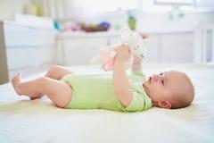 Behandla som ett barn flickan som spelar med hennes favorit- leksak royaltyfria foton