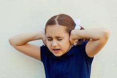 Behandla som ett barn flickan stänger henne öron royaltyfri bild