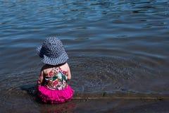 Behandla som ett barn flickasammanträde i vattnet Arkivbild