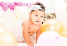 Behandla som ett barn flickasammanträde med kuddar och ballonger Royaltyfri Foto