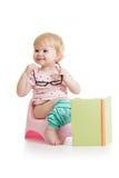 Behandla som ett barn flickasammanträde på chamberpot med boken Royaltyfri Fotografi