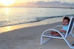 Behandla som ett barn flickasammanträde på en strandstol Arkivfoto