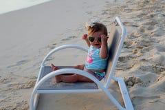Behandla som ett barn flickasammanträde på en strandstol Royaltyfri Foto