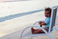 Behandla som ett barn flickasammanträde på en strandstol Arkivfoton