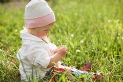 Behandla som ett barn flickasammanträde på gräs Arkivfoto