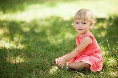 Behandla som ett barn flickasammanträde på gräs Royaltyfri Fotografi