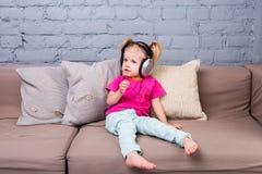 Behandla som ett barn flickasammanträde på soffan med kuddar och att lyssna till musik i pålagt huvud för stor hörlurar Royaltyfria Foton