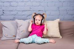 Behandla som ett barn flickasammanträde på soffan med kuddar och att lyssna till musik i pålagt huvud för stor hörlurar Arkivbild