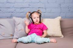 Behandla som ett barn flickasammanträde på soffan med kuddar och att lyssna till musik i pålagt huvud för stor hörlurar Royaltyfria Bilder