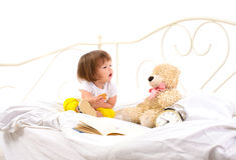 Behandla som ett barn flickasammanträde på vit säng fotografering för bildbyråer