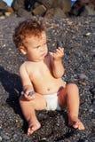 Behandla som ett barn flickastrandlekar med kiselstenar Fotografering för Bildbyråer