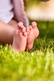 Behandla som ett barn fot i det gröna gräset på sommar som den varma dagen i staden parkerar Royaltyfri Bild