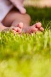 Behandla som ett barn fot i det gröna gräset på sommar som den varma dagen i staden parkerar Fotografering för Bildbyråer
