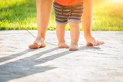 Behandla som ett barn fot som lär att gå ta moment utomhus Arkivbilder