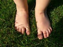 Behandla som ett barn fot på gräs Arkivbilder