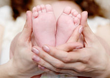 Behandla som ett barn fot som kupas in i moderhänder Royaltyfri Bild