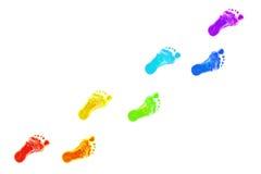 Behandla som ett barn fottryck som allt färgar av regnbågen. Arkivfoton