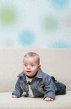 Behandla som ett barn försöket att krypa på soffan Arkivfoto