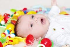 behandla som ett barn Fyra-månader gråta bland leksaker Royaltyfri Bild