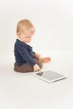 Behandla som ett barn genom att använda den digitala minnestavlan Royaltyfri Foto