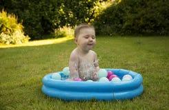 Behandla som ett barn gir som plaskar i en paddla pöl Royaltyfri Foto