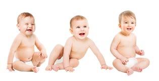 Behandla som ett barn gruppen i blöjor, lyckliga begynnande ungar, litet barnbarn som sitter på vit royaltyfri fotografi