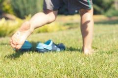 Behandla som ett barn häftklammermatare för blått för ben- och barn` s på det gröna gräset i trädgården, skor för barn, begreppet Arkivbild