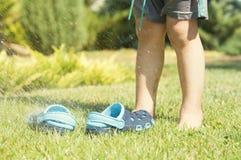 Behandla som ett barn häftklammermatare för blått för ben- och barn` s på det gröna gräset i trädgården, skor för barn, begreppet Fotografering för Bildbyråer