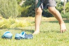 Behandla som ett barn häftklammermatare för blått för ben- och barn` s på det gröna gräset i trädgården, skor för barn, begreppet Arkivbilder