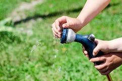 Behandla som ett barn händer närbilden, grön gräsmatta för vatten royaltyfri fotografi