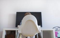Behandla som ett barn hållande ögonen på barns för pojken program för TV Arkivfoton