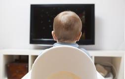 Behandla som ett barn hållande ögonen på tecknade filmer för pojken på TV Fotografering för Bildbyråer