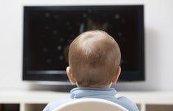 Behandla som ett barn hållande ögonen på tecknade filmer för pojken på TV Arkivbilder