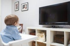 Behandla som ett barn hållande ögonen på television för pojken i vardagsrum Arkivfoton