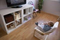 Behandla som ett barn hållande ögonen på television för pojken på hans fåtölj Royaltyfri Bild