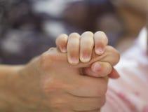 Behandla som ett barn hållande moderns hand Arkivfoto