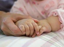 Behandla som ett barn hållande moderns hand Royaltyfria Bilder